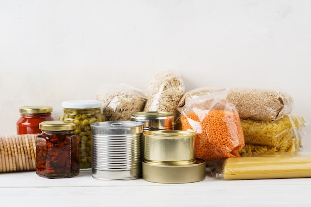Various canned food and raw cereal grains on a table. set of grocery goods for cooking, delivery or donation. copy space.