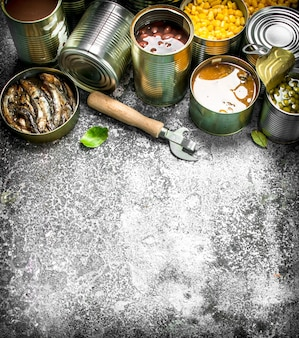 ブリキ缶に肉、魚、野菜、果物が入ったさまざまな缶詰食品。素朴な背景に。