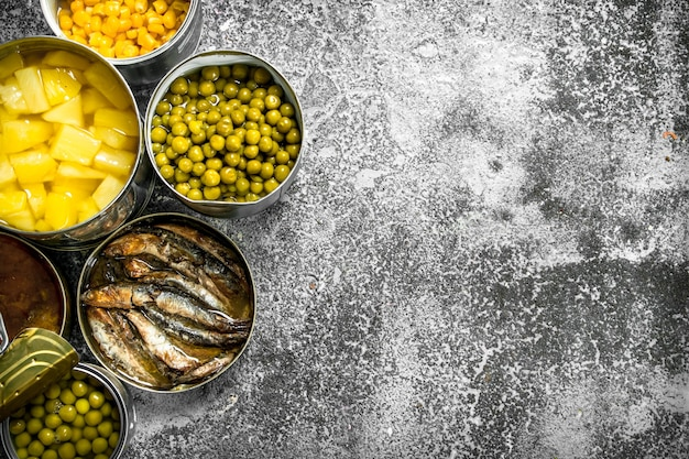 Various canned foods with meat, fish, vegetables and fruits in tin cans on rustic table.