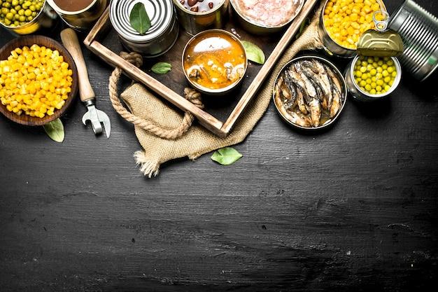 黒い黒板の古いトレイに缶詰のさまざまな缶詰の果物、野菜、魚、肉