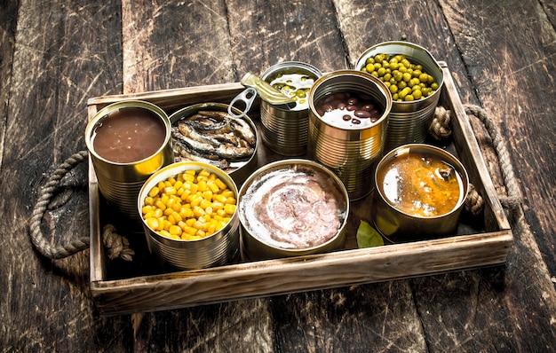 古いトレイのブリキ缶に入ったさまざまな果物、野菜、魚、肉の缶詰。