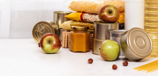 Various canned goods, pasta and cereals on a white table. food donation or food delivery concept.