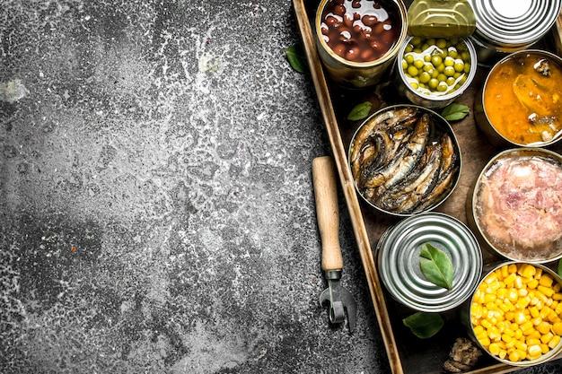 素朴なテーブルの木製トレイに缶詰のさまざまな缶詰製品。