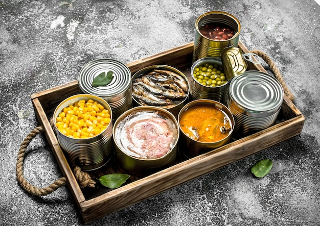 Various canned products in tin cans on wooden tray on rustic table.
