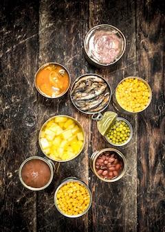 木製のテーブルのブリキ缶にさまざまな缶詰の野菜、肉、魚、果物。