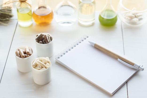 건강 보조 식품, 창조 재료 및 펜이 달린 노트가 들어있는 다양한 캡슐.