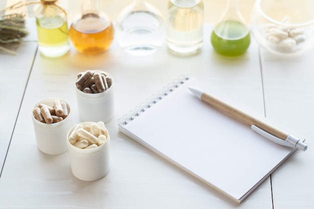 Various capsules with dietary supplements, ingredients for their creation and a notebook with a pen.