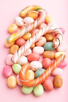 Различные карамельные конфеты на розовой пастели