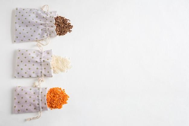 白いコンクリートの背景に散らばっているキャンバスバッグに入った様々なシリアルそば、米、レンズ豆。テキスト用の場所を備えたフラットレイ。