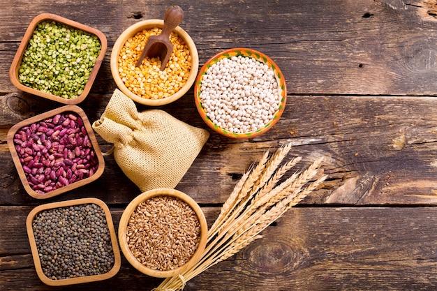 Различные злаки, семена, бобы и зерна на деревянном столе, вид сверху