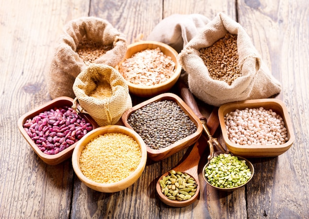 Various cereals, seeds, beans and grains on wooden table