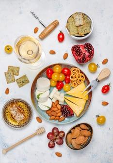 Различный сыр и сырная тарелка на светлом столе с разными орехами и фруктами