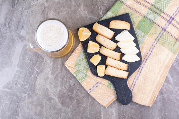 맥주와 함께 어두운 보드에 다양 한 치즈와 레몬 조각. 고품질 사진
