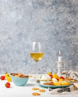 Vari formaggi e piatto di formaggi sul tavolo luminoso con diversi tipi di noci e frutta e bicchiere di vino