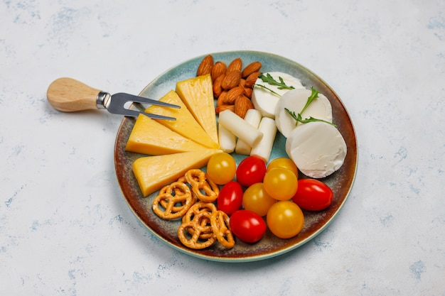 Various cheese and cheese plate on light table with different nuts and fruits