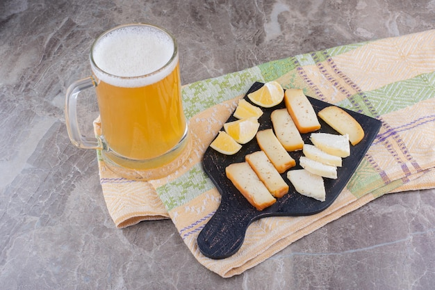 Various cheese and lemon slices on dark board with beer. high quality photo