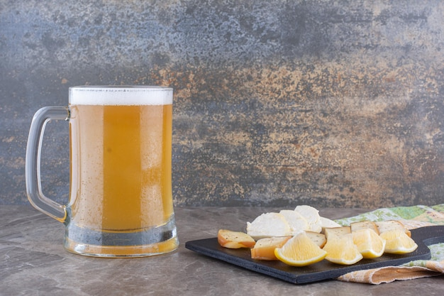 Various cheese and lemon slices on dark board with beer