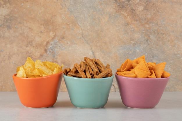 Различные чипсы и крекеры в разноцветных мисках