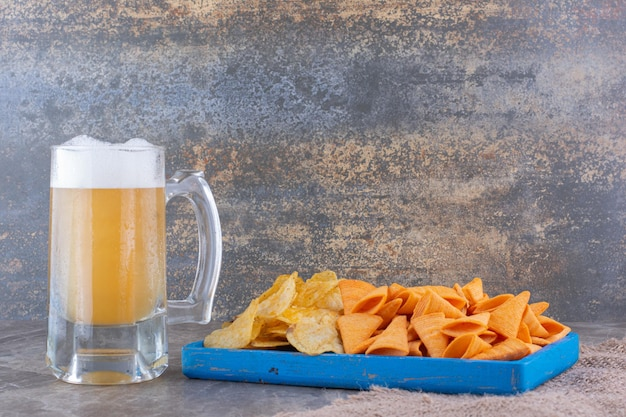 Various chips on blue plate with beer