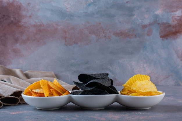 Various chips in a bowl on the marble surface