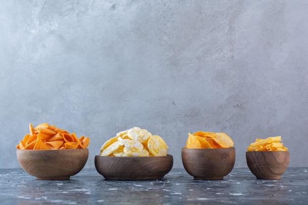 Varie patatine in ciotole, sulla superficie di marmo
