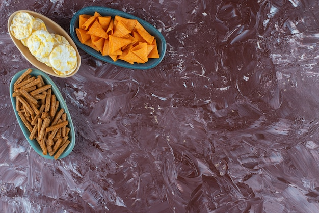 大理石のテーブルの上に、ボウルにさまざまなチップがあります。