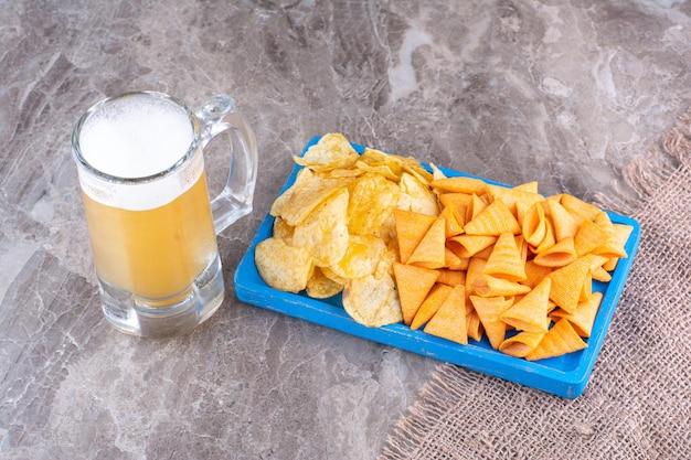 Различные фишки на голубой тарелке с пивом. фото высокого качества