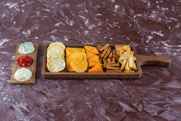 Various chips on serving board with sauce , on the marble table.