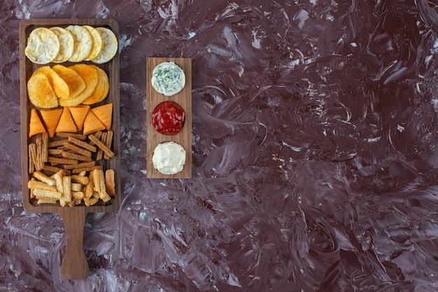 Varie patatine sul tagliere con salsa, sul tavolo di marmo.
