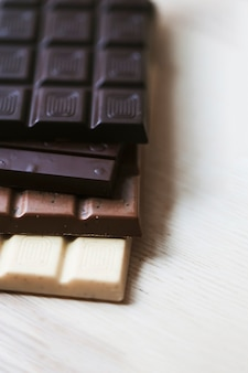 Various chocolate bar stack on wooden textured backdrop