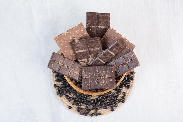 Различные плитки шоколада в деревянной корзине с конфетами. фото высокого качества