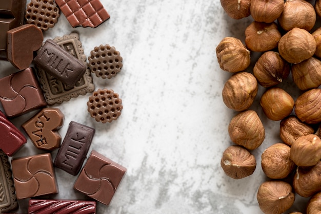 Various chocolate blocks and hazelnuts over white background
