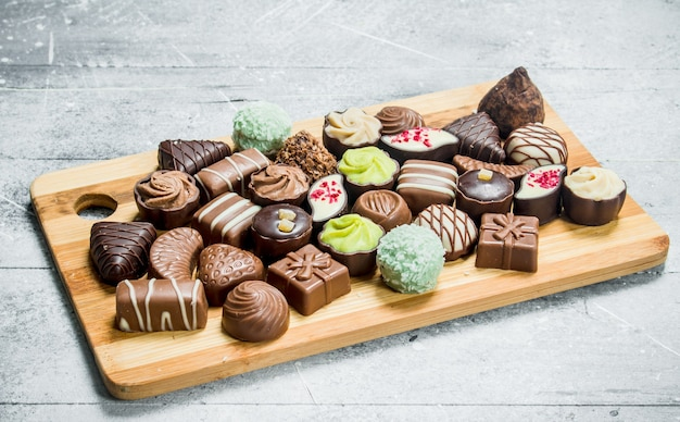 ボード上の様々なチョコレートスイーツ。素朴な背景に。
