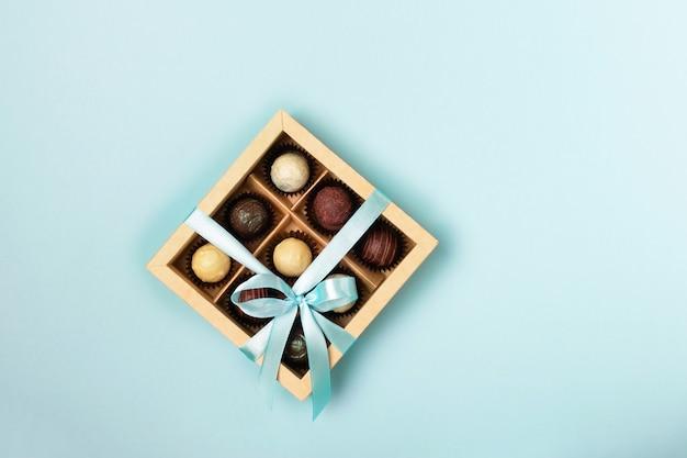 밝은 파란색에 새틴 블루 리본이 달린 종이 상자를 만드는 다양한 초콜릿