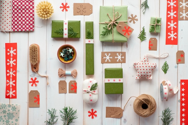 Various christmas or new year winter holiday eco friendly decorations, craft paper packages and reusable gift ideas. geometric flat lay with gift boxes decorated with ribbon, cord and evergreens
