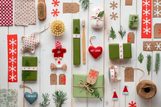 Various christmas or new year winter holiday eco friendly decorations, craft paper packages and reusable or zero waste gifts. flat lay on wood, boxes decorated with ribbon, cord and evergreens.