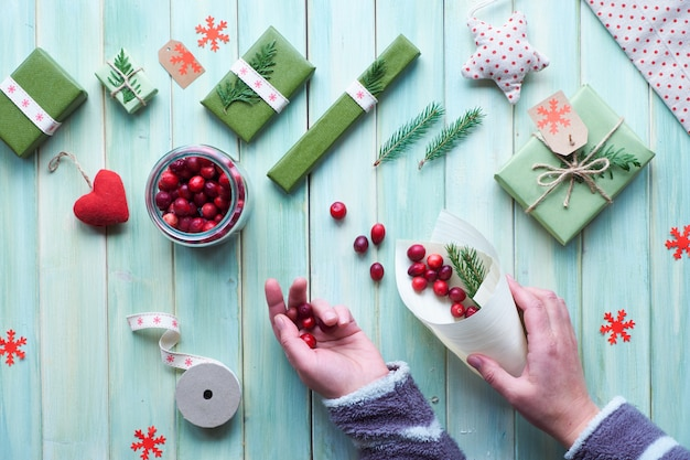 Various christmas or new year winter holiday eco friendly decorations, craft paper packages and reusable or zero waste gifts. flat lay on wood, hands put cranberry in plywood cone with green leaves..