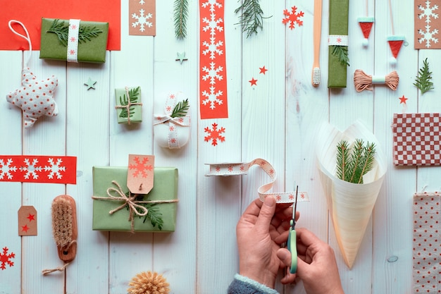 Various christmas or new year winter holiday natural decorations, craft paper packages and eco friendly zero waste gift. flat lay on white wood, hands decorate plywood cone with ribbon and evergreens.