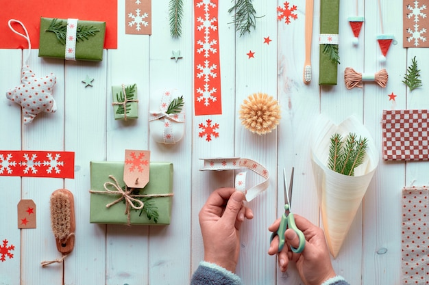 Various christmas or new year winter holiday natural decorations, craft paper packages and eco friendly zero waste gifts. flat lay on wood, hands cutting ribbon to decorate plywood cone..