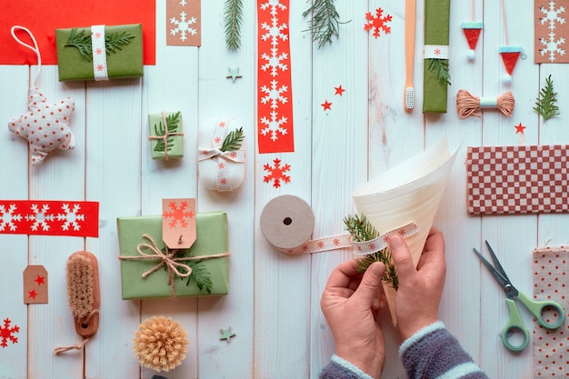 Various christmas or new year winter holiday natural decorations, craft paper packages and eco friendly zero waste gifts. flat lay on wood, hands decorating plywood cone with ribbon and evergreens.