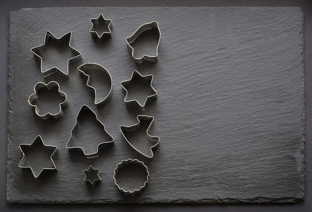 Various christmas-themed cookie cutters on black.