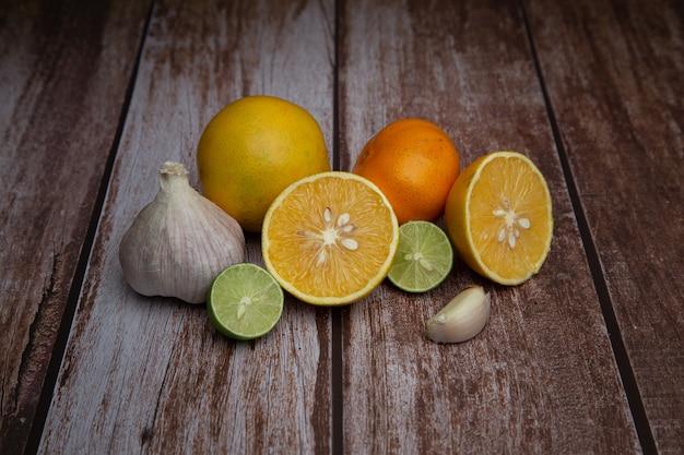 木製の背景を持つ様々な柑橘類とニンニク