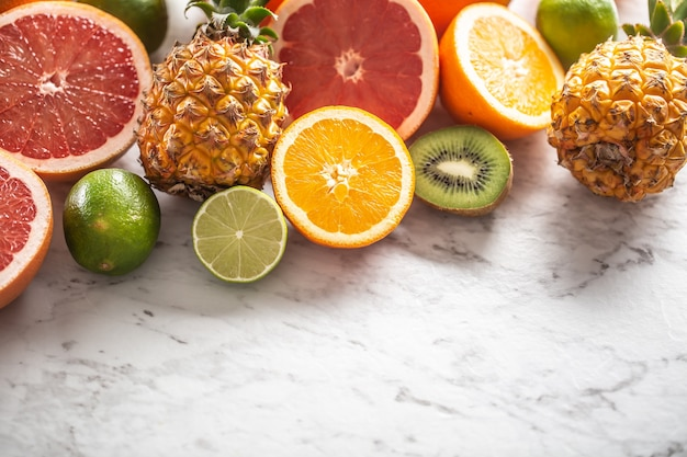Various citruses such as oranges, limes, grapefruits, as well as pineapples on a marble surface.