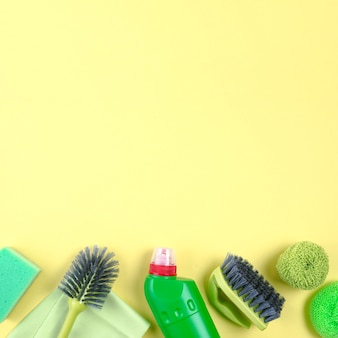 Various cleaning equipments on yellow backdrop