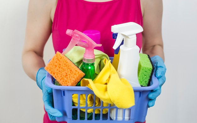 Various cleaning products in the hands of women.