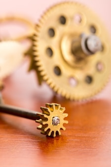 Various clock gears on the wooden table macro