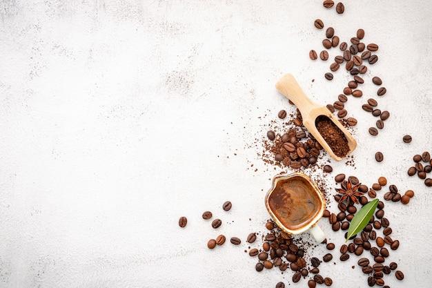 さまざまなコーヒー、ダークローストコーヒー豆、挽いたもの、白いコンクリートの上にスクープを設置したカプセル