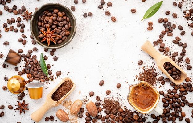 Различный кофе, кофейные зерна темной обжарки, молотый и капсулы с ложками на белом бетоне