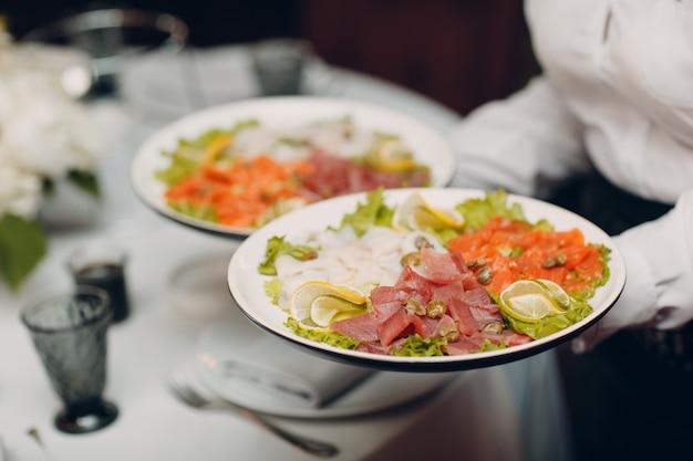 Различные мясные нарезки на тарелке с белыми цветами на столе