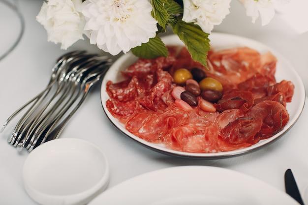 Различные мясные нарезки на тарелке с белыми цветами на столе.